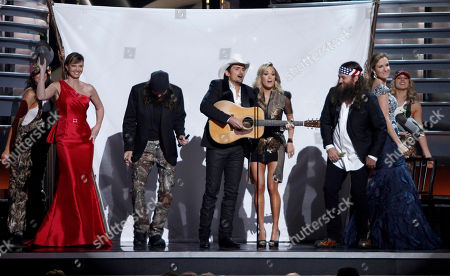 """Co-hosts Brad Paisley, center left, and Carrie Underwood, center right, are seen on-stage with cast members of """"Duck Dynasty"""", Missy Robertson, left, Jase Robertson, second left, Willie Robertson and his wife Korie Robertson, at the 47th annual CMA Awards at Bridgestone Arena, in Nashville, Tenn"""