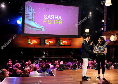 From left, Darren Criss presents Sasha Fisher with an award onstage at the 2013 Do Something Awards, on in Hollywood, Calif