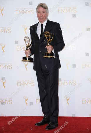 Alan Silvestri poses in the press room with the award for outstanding music direction for a series (original dramatic score) for his work on Cosmos: A Spacetime Odyssey and the award for outstanding main title theme music for his work on Cosmos: A Spacetime Odyssey at the 2014 Creative Arts Emmys at Nokia Theatre L.A. LIVE, in Los Angeles