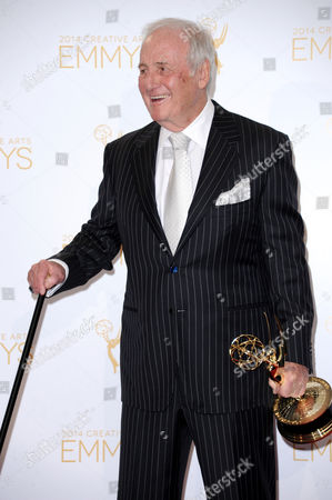 Jerry Weintraub poses in the press room with the award for outstanding documentary or nonfiction series for Years of Living Dangerously at the 2014 Creative Arts Emmys at Nokia Theatre L.A. LIVE, in Los Angeles