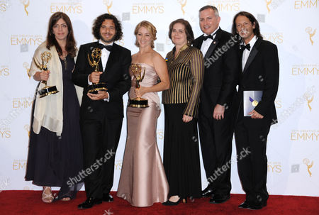 From left, Nancy Abraham, Sean Fine, Andrea Nix Fine, Leslie Gordan, Scott Berns, and Jeff Cosiglio pose in the press room with the award for exceptional merit in documentary filmmaking for Life According to Sam at the 2014 Creative Arts Emmys at Nokia Theatre L.A. LIVE, in Los Angeles