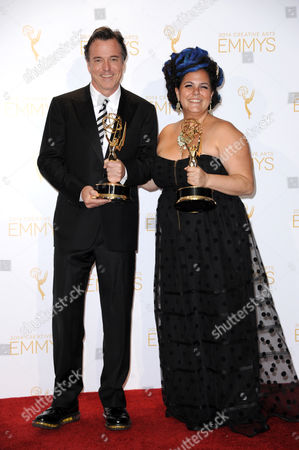 Derek McLane, left, and Gloria Lamb pose in the press room with the award for outstanding art direction for variety, nonfiction, reality or reality-competition for The Oscars at the 2014 Creative Arts Emmys at Nokia Theatre L.A. LIVE, in Los Angeles
