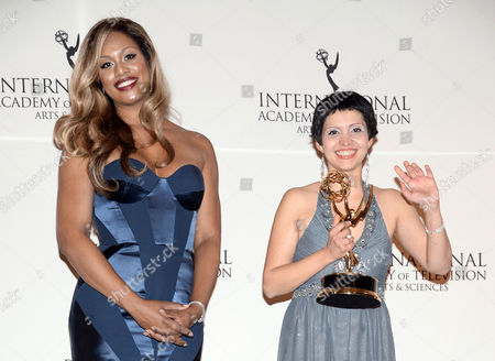 """Documentary"""" award winner Maryam Ebrahimi, right, poses with presenter Laverne Cox in the International Emmy Awards press room at the New York Hilton, in New York"""