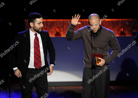 """Eduardo Cabra Martínez, left, and Rene Perez Joglar, of the musical group Calle 13, accept the award for best alternative song for """"El Aguante"""" on stage at the 15th annual Latin Grammy Awards at the MGM Grand Garden Arena, in Las Vegas"""