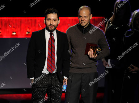 """Visitante, left, and Rene Perez Joglar, of the musical group Calle 13, accept the award for best urban music album for """"MultiViral"""" on stage at the 15th annual Latin Grammy Awards at the MGM Grand Garden Arena, in Las Vegas"""
