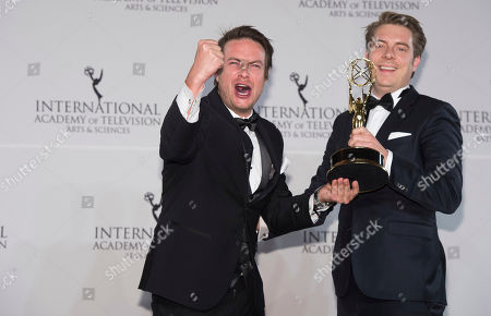 Matthias Bittner, left, and Paul Zischler winners of the Documentary award appear in the press room for the 44th International Emmy Awards at the New York Hilton, in New York
