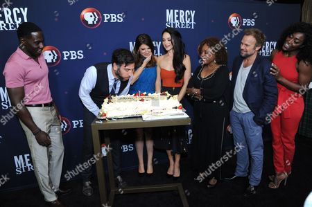 "Josh Radnor, second left left, celebrates his birthday with cast-mates McKinley Belcher III, Tara Summers, Hannah James, L. Scott Caldwell, Norbert Leo Butz and Patina Miller during the ""Mercy Street"" season two portion of the PBS Television Critics Association summer press tour, in Beverly Hills, Calif"