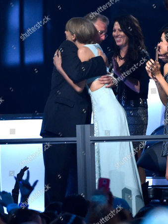 Stock Picture of Scott Kingsley Swift, left, hugs Taylor Swift after she is announced winner of the milestone award at the 50th annual Academy of Country Music Awards at AT&T Stadium, in Arlington, Texas