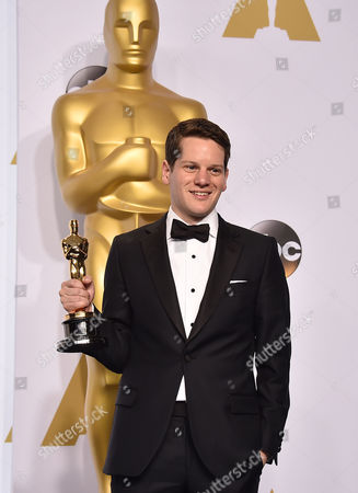 Graham Moore poses in the press room with the award for best adapted screenplay for The Imitation Game at the Oscars, at the Dolby Theatre in Los Angeles