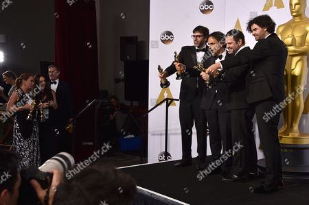"""Nicolas Giacobone, and from left, Alejandro Gonzalez Inarritu, Alexander Dinelaris and Armando Bo pose in the press room with the award for the best picture for Birdman"""" at the Oscars, at the Dolby Theatre in Los Angeles"""