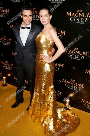 Stock Picture of Couture designer Zac Posen, left, and actress Caroline Correa arrive on the gold carpet of the â?˜As Good As Goldâ?™ premiere, a new short film starring Joe Manganiello that celebrates the U.S. arrival of MAGNUM Gold?! Ice Cream. The film debuted during the Tribeca Film Festival in New York. Visit MagnumIceCream.com for more information