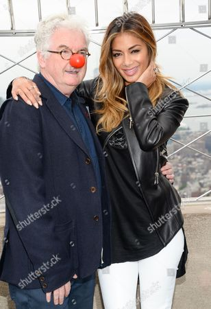 Singer Nicole Scherzinger poses with Comic Relief chief executive Kevin Cahill on the observation deck following the lighting of the Empire State Building in honor of NBC's Red Nose Day entertainment charity event, in New York