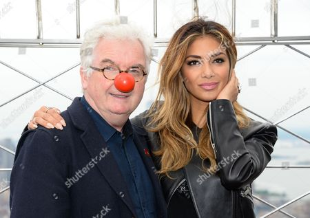 Stock Picture of Singer Nicole Scherzinger poses with Comic Relief chief executive Kevin Cahill on the observation deck following the lighting of the Empire State Building in honor of NBC's Red Nose Day entertainment charity event, in New York