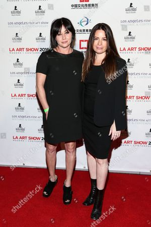 Shannen Doherty, left, and Holly Marie Combs attend The LA Art Show and The LA Fine Art Show Opening Night Premiere Party held at the LA Convention Center, in Los Angeles