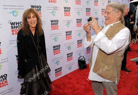 """Music photographer Henry Diltz, right, shoots a photo of fellow photographer Lynn Goldsmith on the red carpet at the """"Who Shot Rock and Roll"""" photo exhibit opening at the Annenberg Space for Photography on in Los Angeles"""