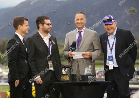 Rob Dyrdek, left, presents the Filly and Mare Sprint trophy at day 2 of the 2014 Breeders' Cup World Championships at Santa Anita Park, in Arcadia, Calif