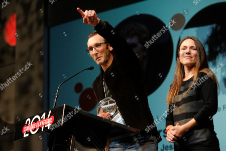 """Jesse Moss, director of """"The Overnighters,"""" accepts the U.S. Documentary Special Jury Award for Intuitive Filmmaking alongside his wife Amanda, a producer on the film, during the 2014 Sundance Film Festival Awards Ceremony, in Park City, Utah"""
