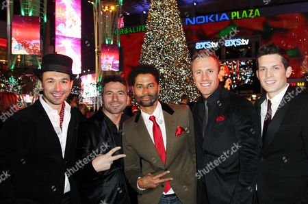 Eric Benet, center, and the The Canadian Tenors pose together at the 5th annual Holiday Tree Lighting at L.A. Live and opening of LA Kings Holiday Ice, in Los Angeles