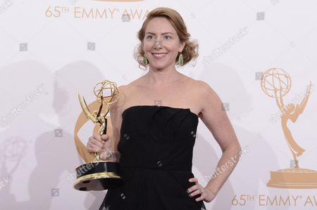 Sarah Bromell poses backstage with the award she accepted on behalf of her husband Writer Henry Bromell for best writing for a drama series award for 'Homeland' at the 65th Primetime Emmy Awards at Nokia Theatre, in Los Angeles