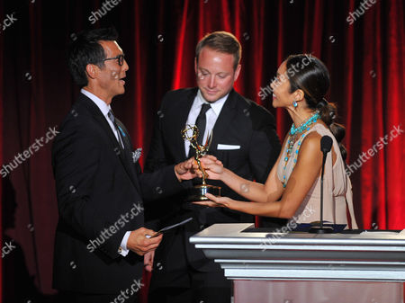 Writer, David Ono of ABC7 accepts the award for outstanding writer - programing from Greg Goldner and Julie Chang on stage at the Television Academy's 66th Los Angeles Area Emmy Awards on at The Leonard H. Goldenson Theater in the NoHo Arts District in Los Angeles