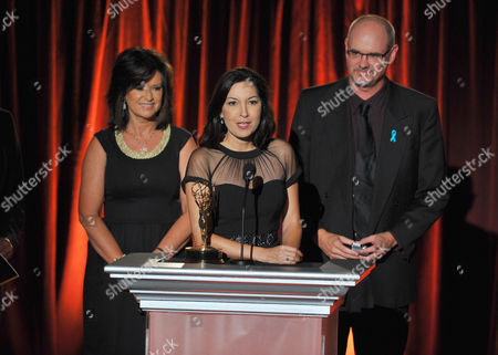 "Beatriz Gomez, Executive Producer of the KMEX news team, center, accepts the award for live special events-programming for ""Fiestas Patrias"" from Dorothy Lucey and David Goldstein at the Television Academy's 66th Los Angeles Area Emmy Awards on at The Leonard H. Goldenson Theater in the NoHo Arts District in Los Angeles"