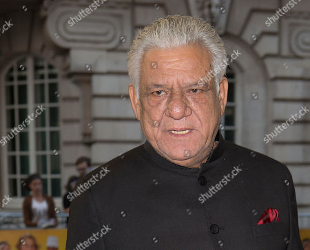British actor Om Puri poses for photographers as he arrives for the UK gala screening of the film The One Hundred Foot Journey, at the Curzon Mayfair in central London, England
