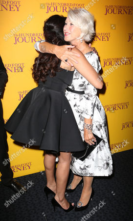 British actress Helen Mirren hugs Farzana Dua Elahe as they arrive for the UK gala screening of the film The One Hundred Foot Journey, at the Curzon Mayfair in central London, England