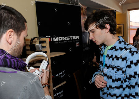 Actor Alex Shaffer, right, learns about Inspiration headphones by Monster Products at the Fender Music lodge during the Sundance Film Festival, in Park City, Utah