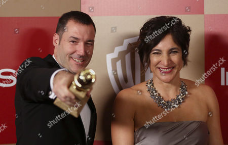 "Director Mark Andrews, left, and Katherine Sarafian pose with the award for best animated feature film for ""Brave"" arrives at the InStyle and Warner Bros. Golden Globe After Party at the Beverly Hilton Hotel, in Beverly Hills, Calif"