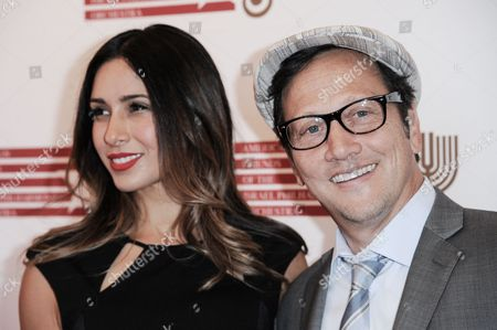 Patricia Azarcoya Arce, left, and Rob Schneider arrive at the Israeli Philharmonic Orchestra Honors Hans Zimmer held at the Wallis Annenberg Center for the Performing Arts, in Beverly Hills, Calif