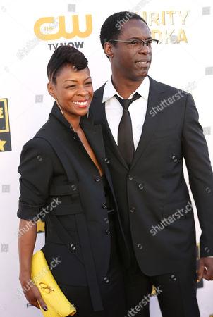 Jenisa Garland, left, and Isaiah Washington arrive at the 19th annual Critics' Choice Movie Awards at the Barker Hangar, in Santa Monica, Calif