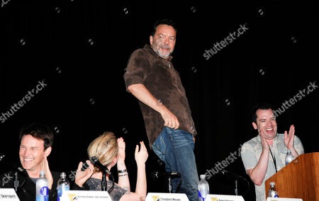 Director Alan Ball stands on a chair as he rolls his belly as actor Stephen Moyer, far left, actress Anna Paquin, left, and moderator Tim Stack, right, look on during the True Blood panel on the third day of Comic-Con convention held at the San Diego Convention Center, in San Diego