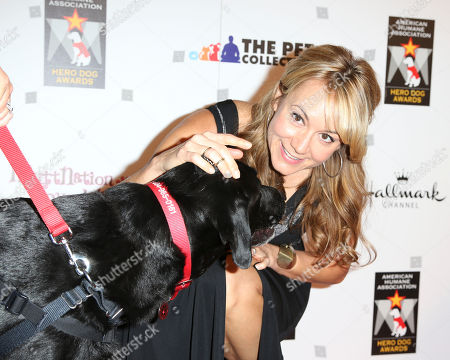 Actress Megyn Price greets Search and Rescue Dog Winner Soot during 2012 American Humane Association Hero Dog Awards held at the Beverly Hilton Hotel, in Los Angeles, Calif