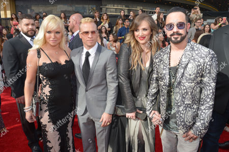 Second from left, Brian Littrell, and far right, A.J. McLean, of the musical group The Backstreet Boys, and from left Leighanne Littrel and Rochelle Karidis arrive at the 2014 MTV Movie Awards, on in Los Angeles