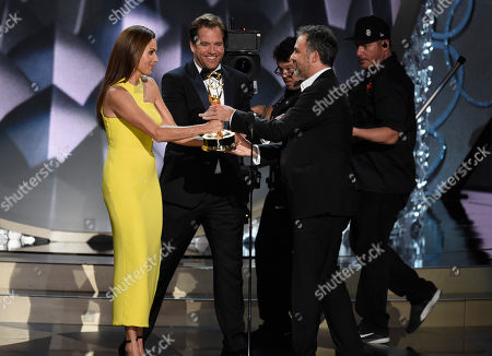 Miguel Sapochnik, from right, accepts the Outstanding Directing for a Drama Series for 'Game of Thrones' episode 'Battle of the Bastards' from actors Michael Weatherly and Minnie Driver at the 68th Primetime Emmy Awards, at the Microsoft Theater in Los Angeles