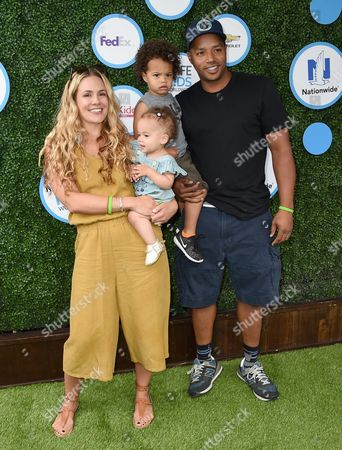 CaCee Cobb, left, Donald Faison, right, and their children, from second left, Wilder and Rocco, arrive at Safe Kids Day at Smashbox Studios, in Culver City, Calif