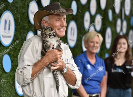 Jack Hanna carries a cloud leopard as he arrives at Safe Kids Day at Smashbox Studios, in Culver City, Calif