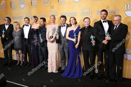 From left, David O. Russell, Colleen Camp, Alessandro Nivola, Jennifer Lawrence, Michael Pena, Elisabeth Rohm, Jeremy Renner, Amy Adams, Paul Herman, Bradley Cooper and Robert De Niro pose in the press room with the award for outstanding performance by a cast in a motion picture for American Hustle at the 20th annual Screen Actors Guild Awards at the Shrine Auditorium, in Los Angeles