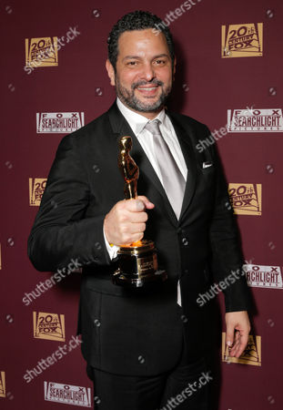 Alexander Dinelaris, Jr. is seen with his award for best original screenplay at the 20th Century Fox & Fox Searchlight Oscar Party at BOA Steakhouse, in West Hollywood, Calif
