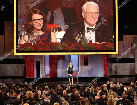 Stock Image of Tina Fey speaks at the 43rd AFI Lifetime Achievement Award Tribute Gala at the Dolby Theatre, in Los Angeles. Honoree Steve Martin on right and Anne Stringfield appear on the screen