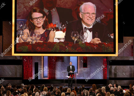 Steve Carell speaks at the 43rd AFI Lifetime Achievement Award Tribute Gala at the Dolby Theatre, in Los Angeles. Honoree Steve Martin on right and Anne Stringfield appear onscreen
