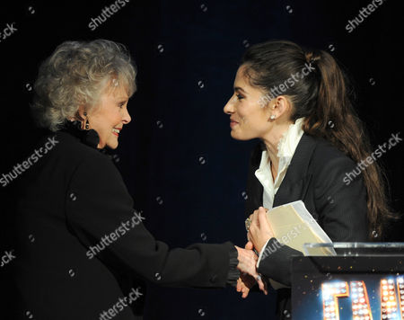 Host Sarah Shahi, right, greets actress June Lockhart onstage at the 65th Primetime Emmy Engineering Awards,, at Loews Hollywood Hotel, in Hollywood, Calif