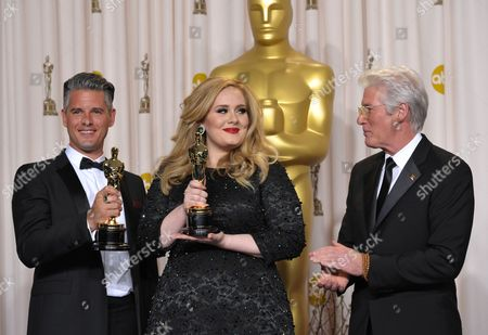 "Adele and Paul Epworth pose with their award for best original song for ""Skyfall"" with presenter Richard Gere during the Oscars at the Dolby Theatre, in Los Angeles"