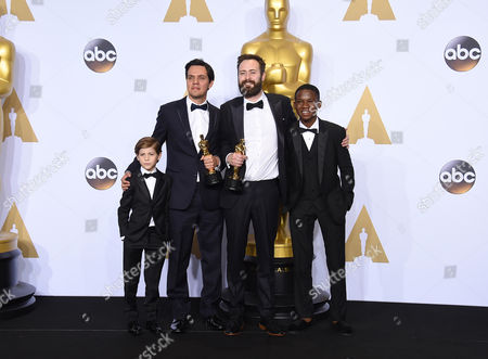 Jacob Tremblay, left, and Abraham Attah, right, pose in the press room with Shan Christopher Ogilvie, left, and Benjamin Cleary, winners of the award for best live action short film for Stutterer, at the Oscars, at the Dolby Theatre in Los Angeles