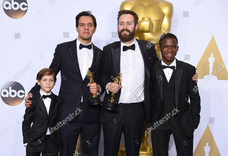 Jacob Tremblay, left, and Abraham Attah, right, pose in the press room with Shan Christopher Ogilvie, second left, and Benjamin Cleary, winners of the award for best live action short film for Stutterer, at the Oscars, at the Dolby Theatre in Los Angeles