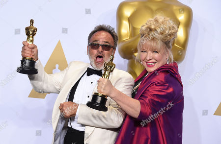 Colin Gibson, left, and Lisa Thompson pose with the award for best production design for â?œMad Max: Fury Roadâ?? in the press room at the Oscars, at the Dolby Theatre in Los Angeles