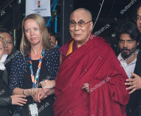 Festival organiser Emily Eavis escorts the Dali Lama on stage during Patti Smiths performance at the Glastonbury music festival on at Worthy Farm, Glastonbury, England