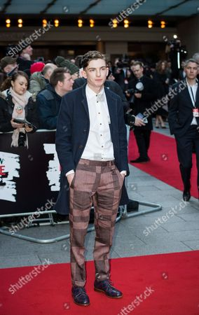 Bill Milner poses for photographers upon arrival at the Empire Film Awards in London