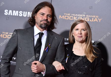 """Peter Craig, left, and Suzanne Collins attend the Los Angeles premiere of """"The Hunger Games: Mockingjay - Part 2"""" at the Microsoft Theater on"""