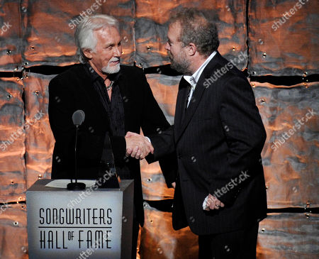 Singer Kenny Rogers, left, introduces inductee Don Schlitz at the 2012 Songwriters Hall of Fame induction and awards gala at the Marriott Marquis Hotel, in New York